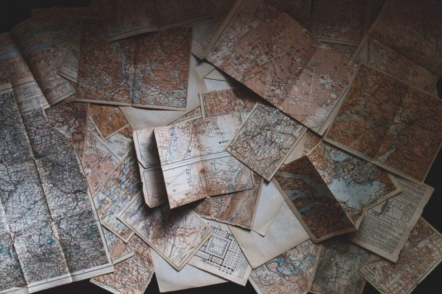 Faded maps overlapping and strewn across a table.