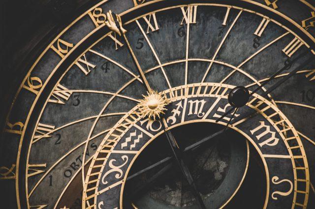 Close up of elaborate black and gold clock.