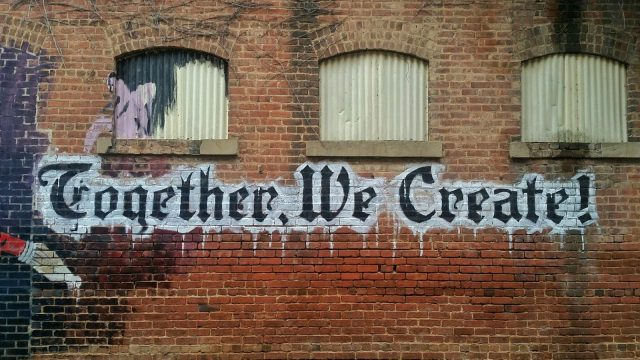 """Together we create"" graffiti-ed on a brick wall"