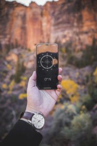 A hand holds up a compass on a phone.