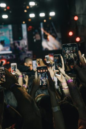 Lots of people hold smartphones up to take a photo