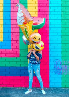Person holding balloons shaped like emoticons against a brightly painted wall