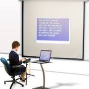 Drawin of a person typing at a computer. Their words are displayed on a large screen/