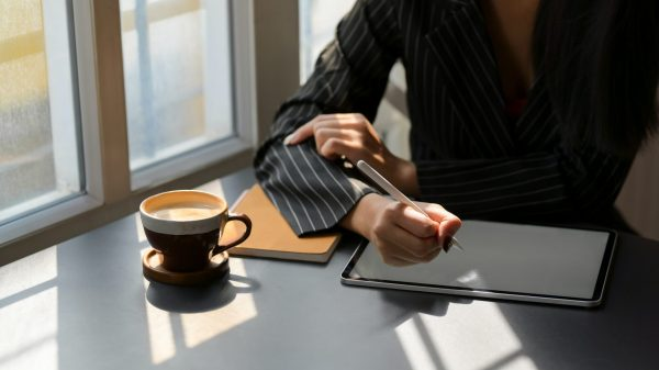 woman writing in a digital notepad while drinking coffee