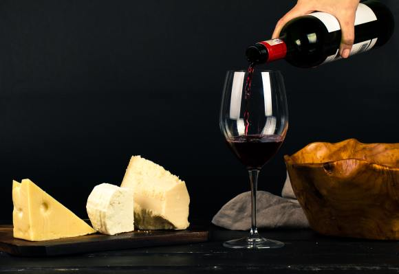 Cellar Worthy Wine A glass of red wine surrounded by different cheeses with a wooden a bowl and napkin