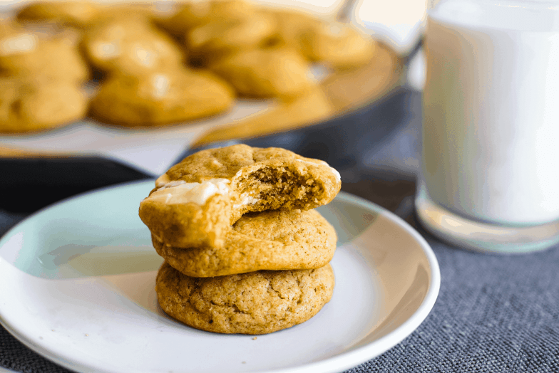 Three pumpkin brown butter white chocolate chunk cookies stacked on top of each other with a bite taken out of the top cookie revealing its chewiness.