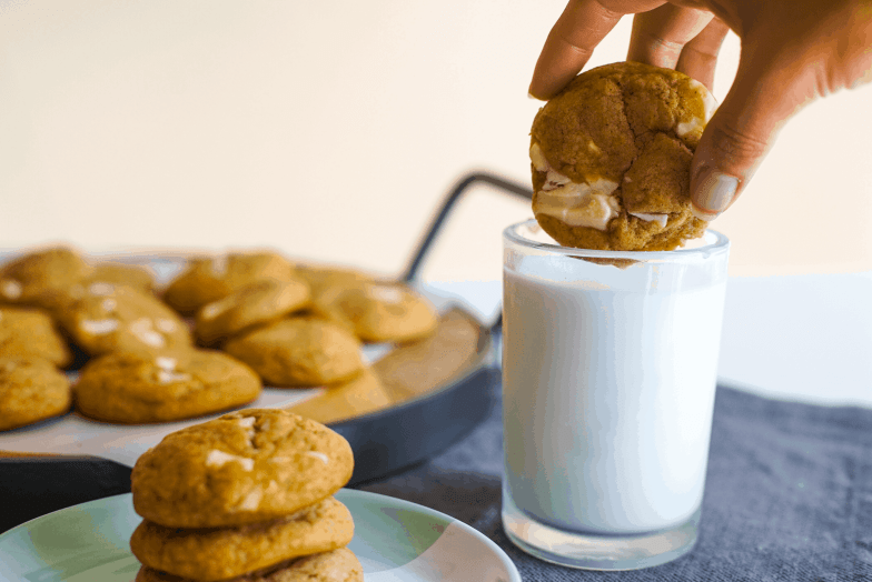Hand dunking a pumpkin brown butter white chocolate chunk cookie into a glass of milk next to more cookies.