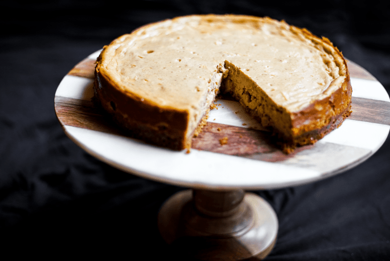 Spiced apple cheesecake with a slice missing on a marble and wood cake stand.