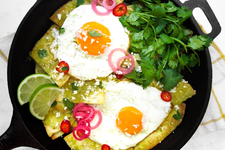 Skillet of air fryer chilaquiles verdes with sunny side up eggs and pickled red onions, garnished with cilantro and lime wedges.