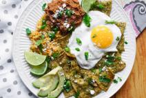 Plate of air fryer chilaquiles verdes with a sunny side up egg and side of rice and beans.