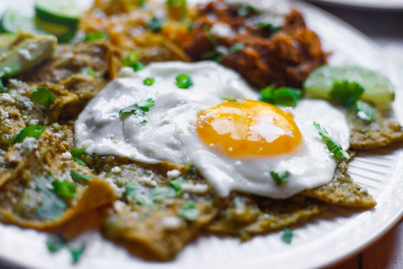 Close up of a sunny side up egg lying on top of air fryer chilaquiles verdes.