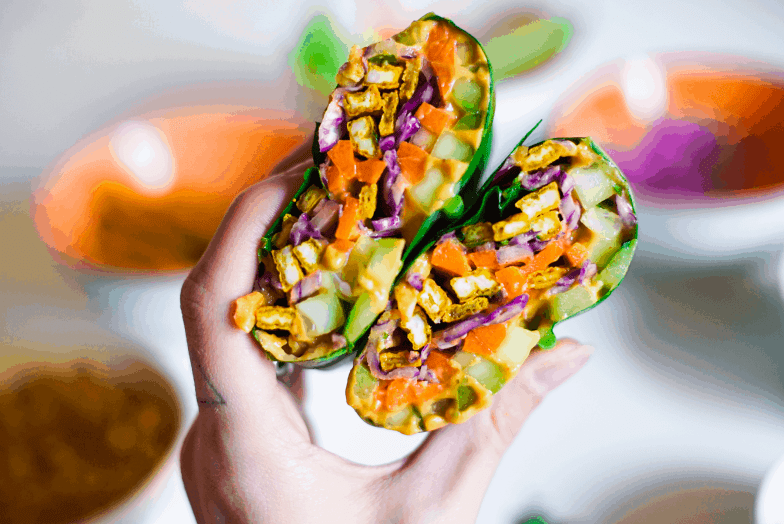 Close up of a hand holding a colorful vegetarian wrap made from collard green leaves.