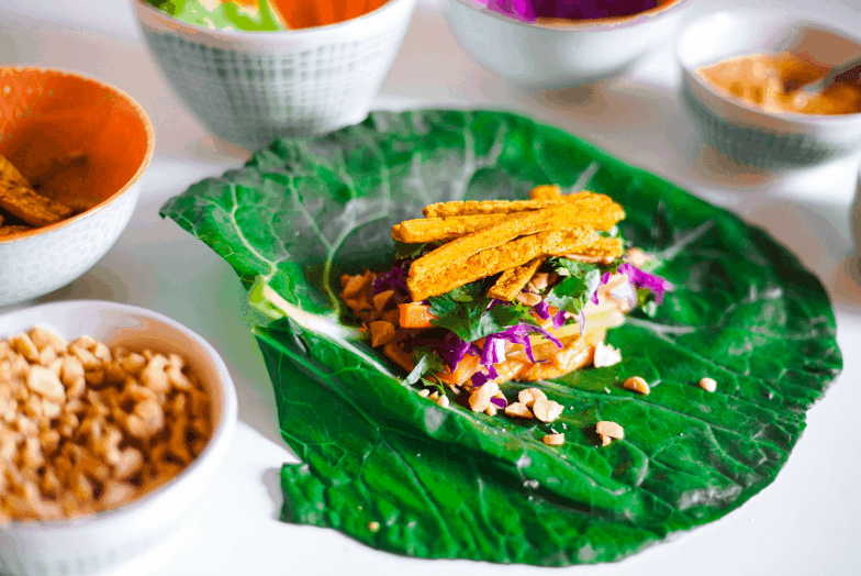 Collard green leaf piled high with colorful vegetables and tofu, surrounded by small bowls filled with the ingredients.