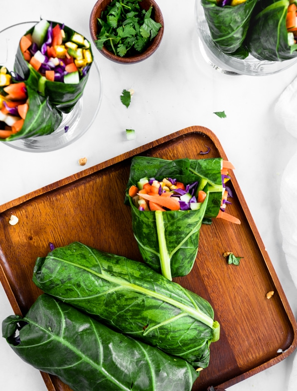 And array of rainbow wraps filled with colorful veggies wrapped in collard greens. Some wraps are whole and some cut in half to reveal the colorful veggies.