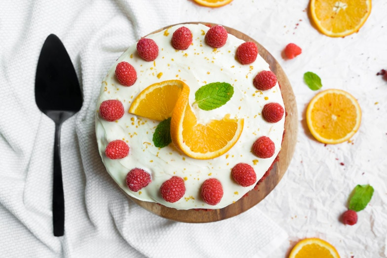 Orange scented red velvet cake decorated with vibrant red raspberries and orange slices.