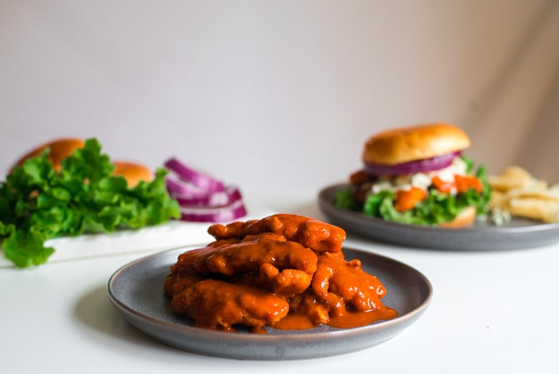 Plate stacked with buffalo chicken tenders next to a buffalo chicken sandwich.