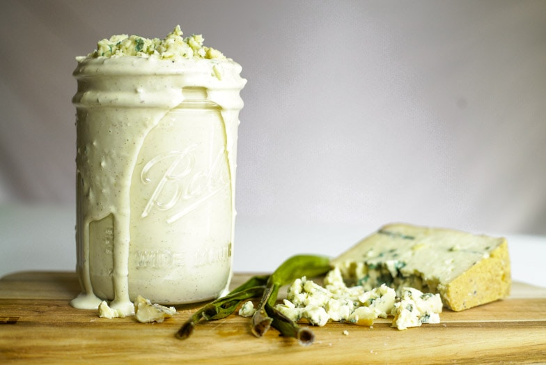Jar overflowing with smoky blue cheese dressing next to a wedge of smoked blue cheese and roasted green onions.