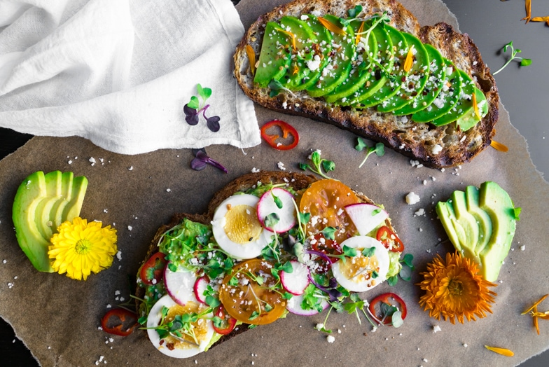 Two slices of spring avocado toast with hard boiled eggs, radishes, and edible flowers.