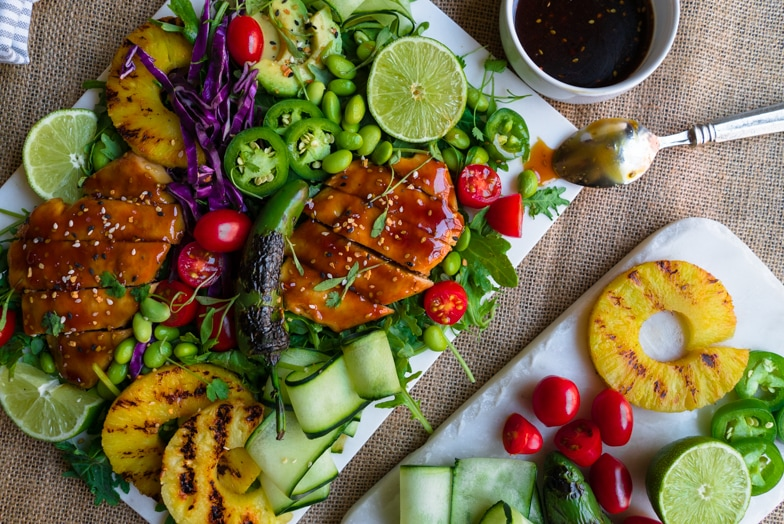 Colorful teriyaki chicken salad with grilled pineapple and fresh lime next to a platter of fresh ingredients.