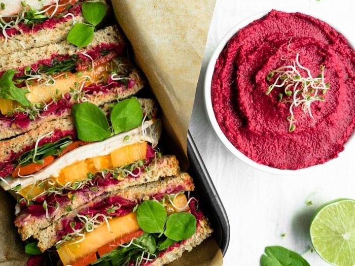 Rainbow veggie and turkey sandwich next to bowl of vibrant roasted beet hummus.