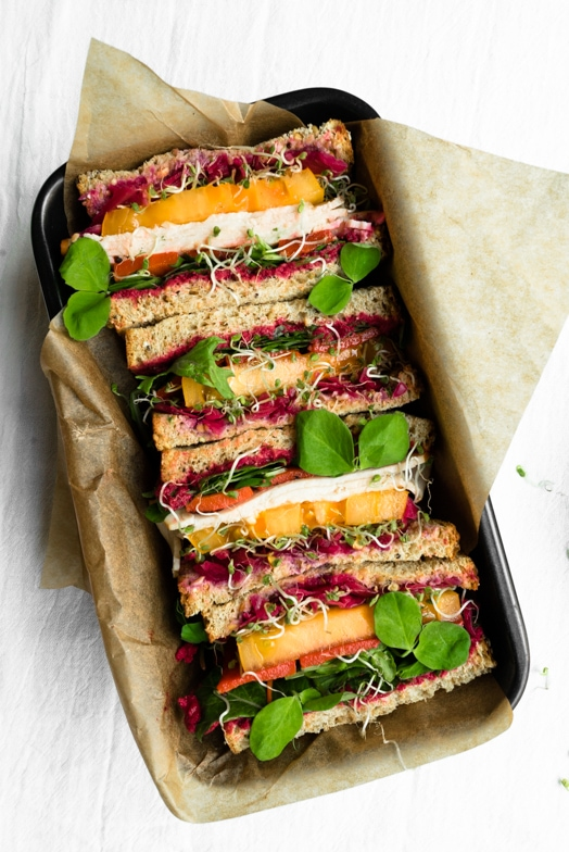 Rainbow veggie and turkey sandwich with vibrant roasted beet hummus.