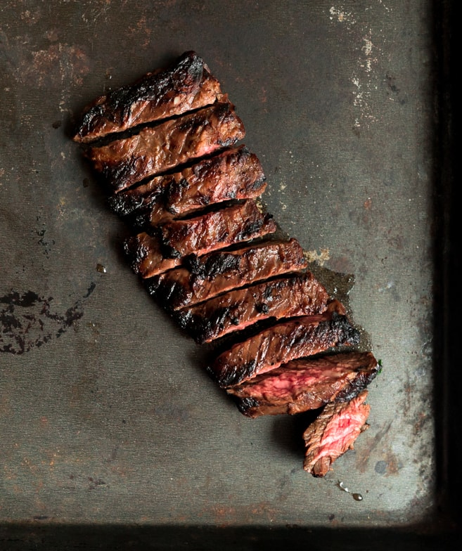 Juicy, medium-rare skirt steak cut into slices on a rustic pan.