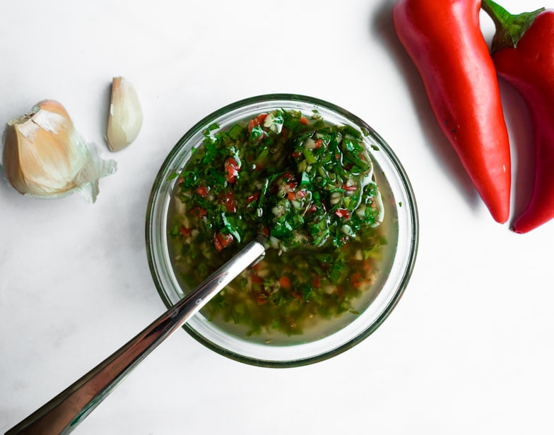 Fresh green chimichurri sauce in a bowl next to red chili peppers and garlic.