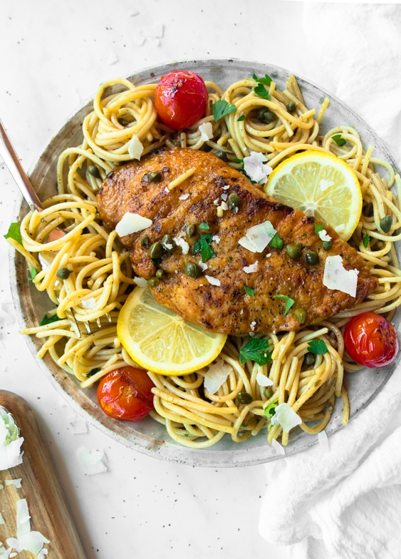 Rustic bowl of spaghetti topped with lemony chicken piccata and burst cherry tomatoes.