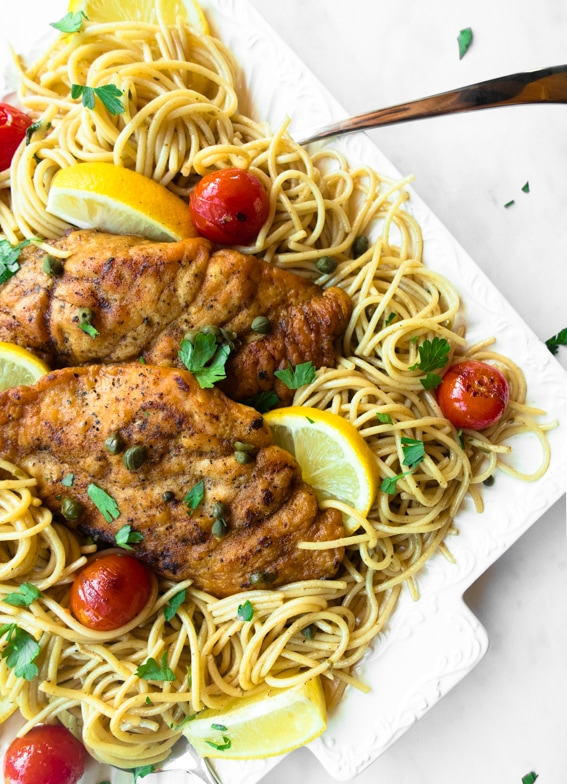 Close up of lemony chicken piccata with burst cherry tomatoes over spaghetti.