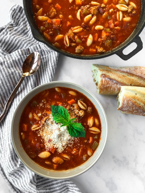 Pot of spicy pasta e fagioli with parmesan, fresh basil, and rustic bread.