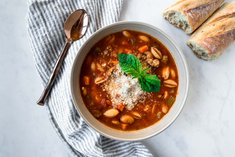 Bowl of spicy pasta e fagioli with parmesan cheese, basil, and rustic bread.