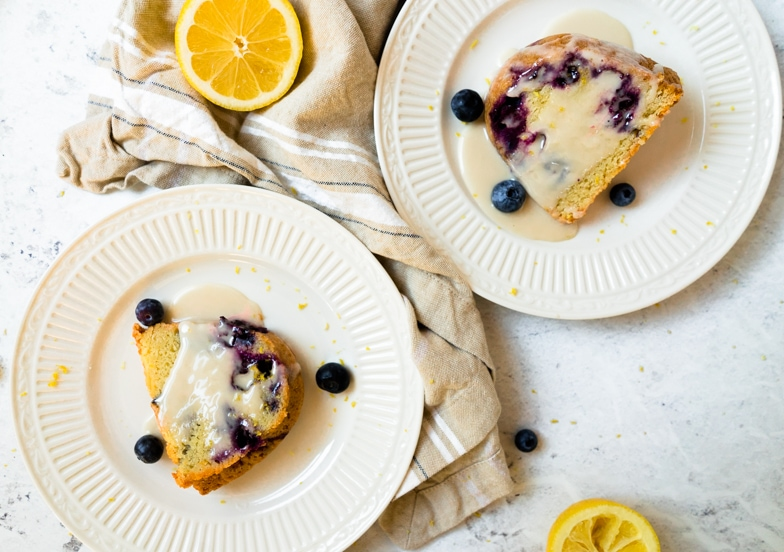 Two pieces of blueberry muffin cake on dessert plates drizzled with an extra serving on lemon glaze.