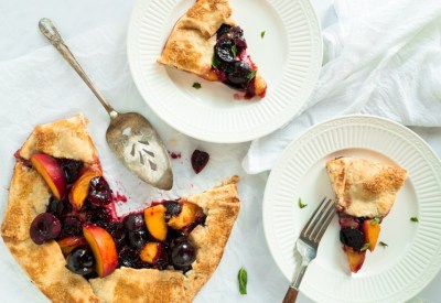 Two slices of cherry peach goat cheese galette on plates garnished with fresh basil. Click to view recipe!