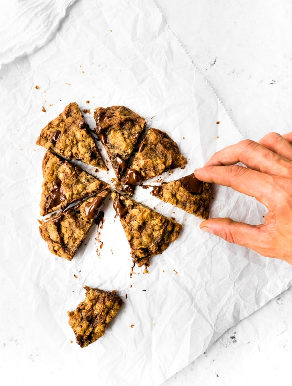 Giant pumpkin spice oatmeal cookie with melty chocolate chunks cut into slices with a hand snatching one.