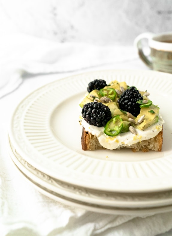Slice of avocado toast with blackberries, serrano peppers, and honey black pepper whipped ricotta on top of a stack of plates.