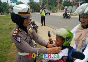 Kasat Lantas Polres Aceh Timur, AKP Nita Febrianti saat memasangkan helm kepada pengguna jalan dalam operasi Simpatik Rencong Bandar 2016. (Photo / GoAceh.co/ Asra)