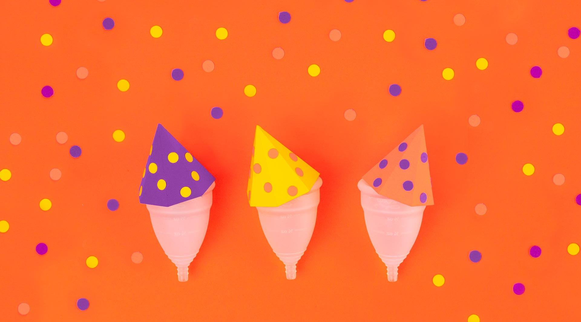 Three DivaCups wearing polka dotted paper party hats surrounded by paper confetti dots on a vibrant orange background.