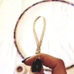 Picture of a hand holding a loop knot on twine above a purple hula hoop and white background