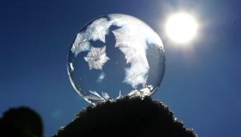 zarte Seifenblase eingefroren mit Eisblumen wird von Sonnenstrahlen beschienen