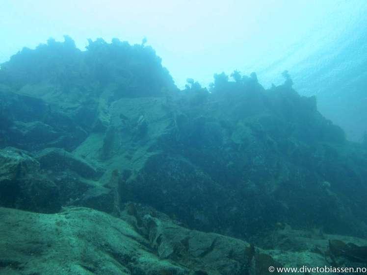 Klart vann, bergveggg, (Silfra på Island)