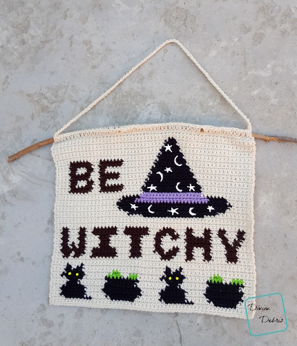 """[Image description] A crochet wall-hanging, a cream background with the with the words """"Be Witchy"""" in two lines and in all caps in the color brown. To the right of the words is a conical black witch hat with a purple band and added stars and moons in white puffy pain. Along the bottom of the wall-haning are black cats with yellow eyes and black cauldrons with green bubbles"""