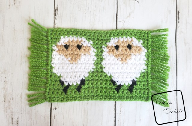 [image description] Simple rectangular sheep design, white sheep on a green background, with fringe on the side. The Dancing Sheep Mug Rug