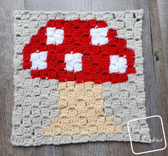 [Image description] C2C Mushroom Afghan Square laying in the center of the frame on a wood-grain background.