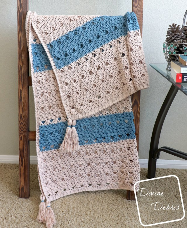 [Image description] Tan and blue Louise Blanket crochet pattern is draped over a blanket ladder, tassels forward, with a table to the right of the blanket
