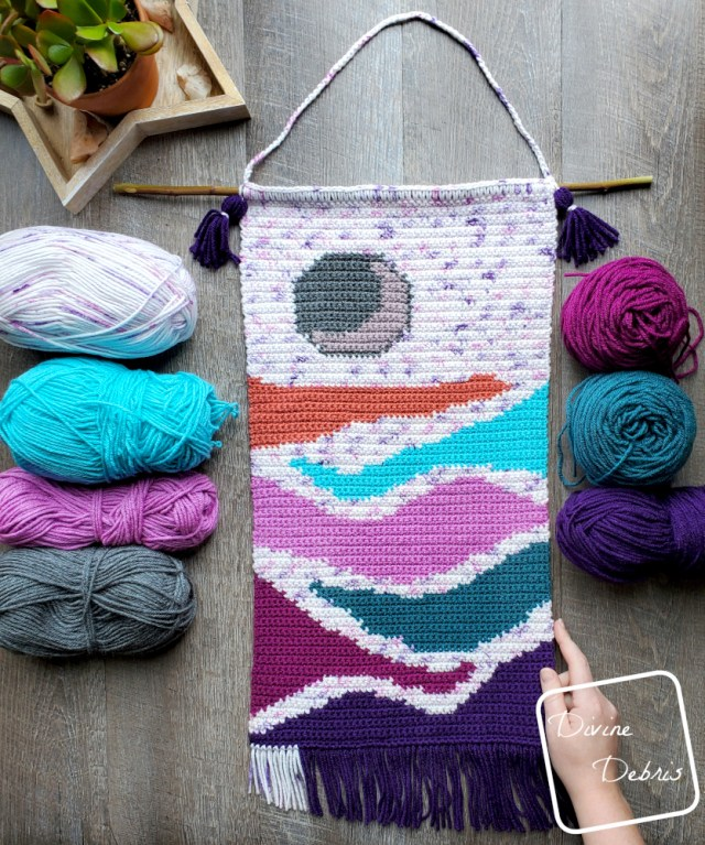 [Image description] Moon Rise Wall-Hanging laying flat on a wood grain background with four skeins of yarn on the left and 3 on the right with a white woman's hand holding on the bottom right corner.