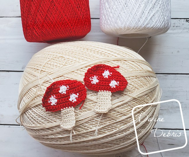 [Image Description] 2 Red topped crochet mushrooms sit on top of a tan skein of crochet thread and a skein of white and red thread are visible at the top of the photo