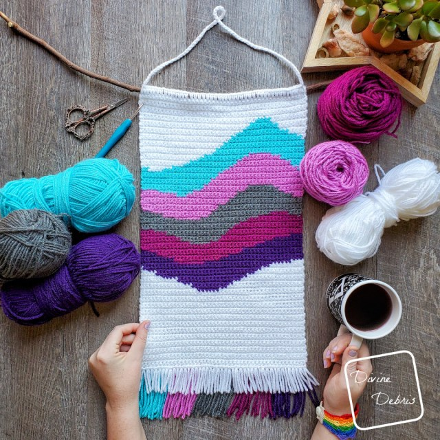 [Image description] the 6 color Cool Waves Wall-Hanging lays in the middle of the frame, 3 skeins of yarn on the left and 2 cakes and a skein on right. A white woman's hand is holding onto the left side and a cup of coffee on the bottom right.