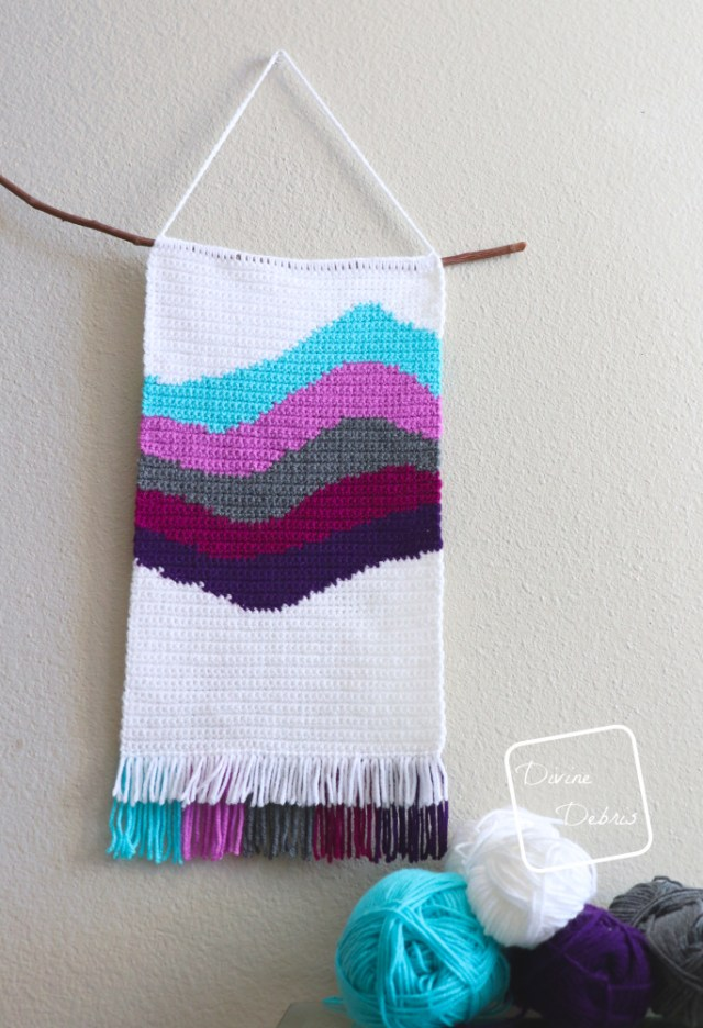 [Image description] The Cool Waves Wall-Hanging hangs on a off-white wall slightly off center with skeins of yarn on the lower right-hand of the photo.