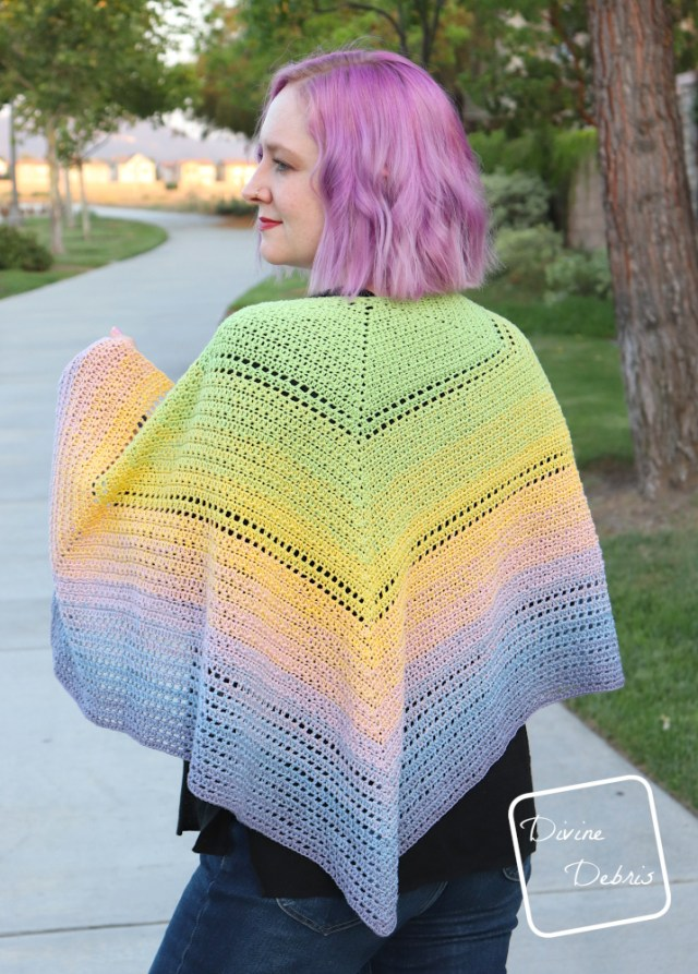 [Image description] A white woman with purple hair stands facing away from the camera while her shoulders are draped with the Alix Shawl in multi-colored pastels, up towards the camera