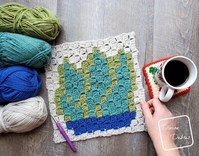 [Image description] the C2C Agave Square lays flat on a wood grain background, a white woman's hand holds the bottom right corner, 4 skeins of yarn sit on the left and a cup of coffee sits on the right.